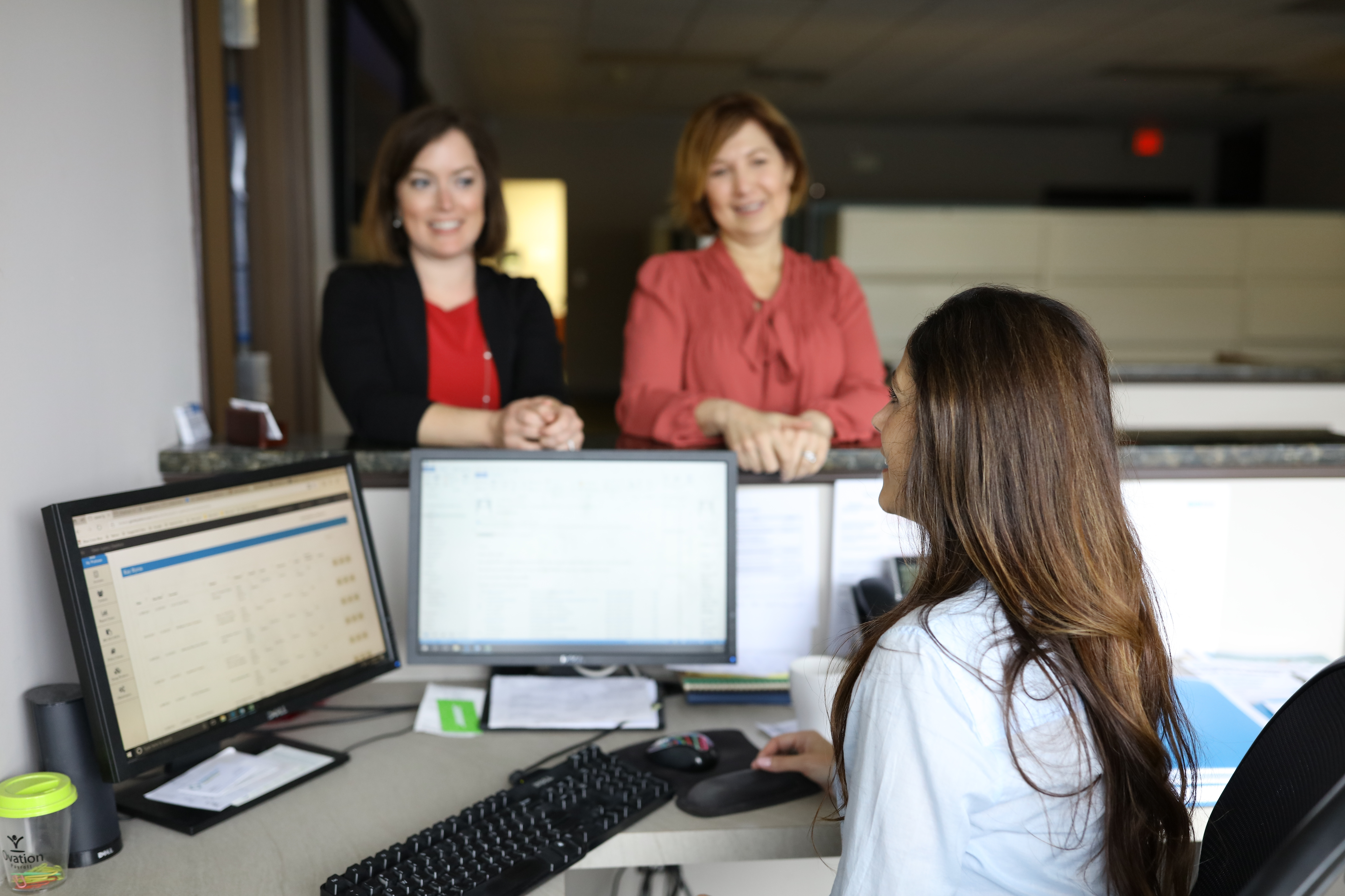 Women standing in front of managers desk chatting