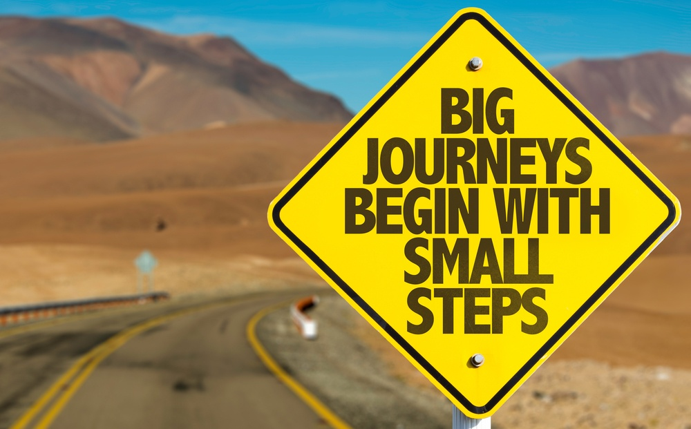 Big Journeys Begin With Small Steps sign on desert road. need help.