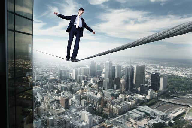 Business man balancing on the rope high in the sky.jpeg
