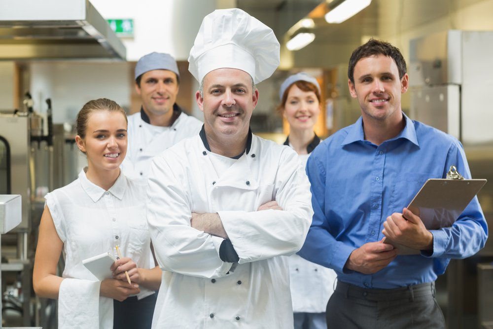 Head chef posing with the team behind him in a profesionnal kitchen