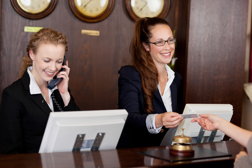 Two beautiful young stylish receptionists at a reception desk, one talking on the telephone and the other handing a card to a customer
